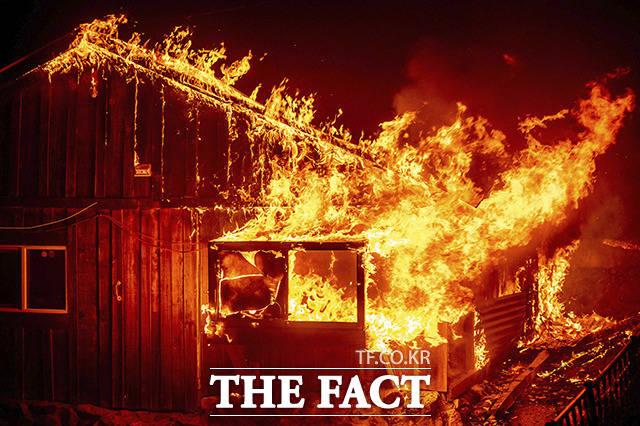 낙뢰로 촉발된 산불이 번지면서 불에 타고 있는 가정집.