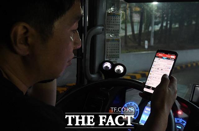 업무의 끝은 새로운 시작 새벽 첫 배송 업무를 마친 김 씨가 휴대폰 앱에서 새로운 일을 찾고 있다.