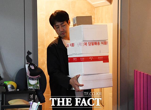 배송된 스티로폼 박스를 집 안으로 들고 들어오는 김 씨.