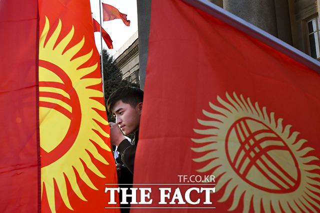 14일(현지시간) 키르기스스탄 수도 비슈케크의 정부청사 앞에서 한 시위 참가 남성이 주도자의 연설을 듣고 있다. /비슈케크=AP.뉴시스