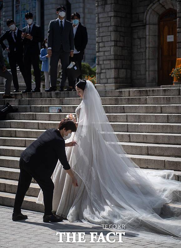 코로나19 중에 결혼식을 올린 신부는 걱정 가득한 표정으로 사진 촬영을 준비하고 있다.