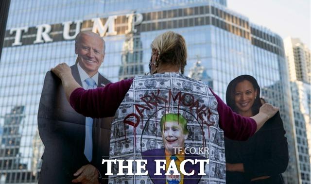 7일(현지시간) 미 일리노이주 시카고에서 한 여성이 조 바이든과 카멀라 해리스 형상의 선간판을 붙잡고 이들의 대선 승리를 축하하고 있다. 바이든 민주당 후보는 경합 주인 펜실베이니아주에서 승리하면서 선거인단 273석을 확보, 도널드 트럼프 대통령을 꺾고 미국의 제46대 대통령이 됐고 해리스 후보는 흑인 여성 최초의 부통령이 됐다. /시카고=AP.뉴시스