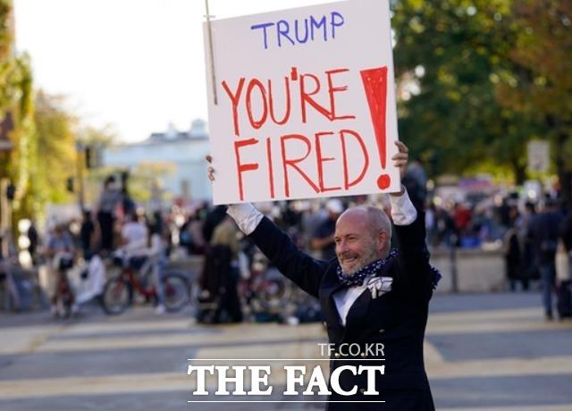 6일(현지시간) 미 워싱턴 백악관 인근 흑인 생명 소중(BLM) 광장에서 시위대가 모든 표의 개표를 촉구하는 시위를 하는 가운데 한 남성이 트럼프, 해고라는 팻말을 들고 있다. /워싱턴=AP.뉴시스