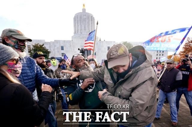 7일(현지시간) 미 오리건주 주도 세일럼에 있는 오리건주 의사당 앞에서 도널드 트럼프 대통령의 지지자(왼쪽)가 바이든 지지자와 주먹다짐을 벌이며 싸우고 있다. /세일럼=AP.뉴시스