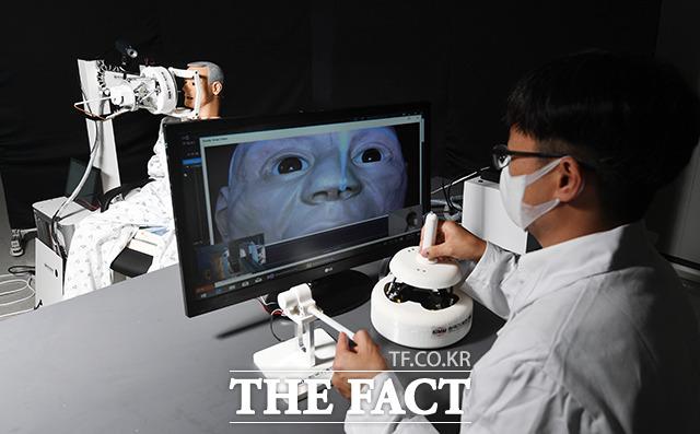 <가속화 IT산업> 코로나19 검체 채취하는 의료진들의 감염 위험을 최소화시키기 위해 제작된 코로나19 비대면 원격 검체 채취 로봇. 한국기계연구원 대구융합기술연구센터 서준호 박사가 검체 채취를 시연하고 있다.