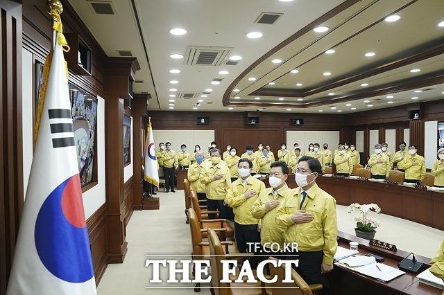 문재인 대통령이 지난 3월 17일 서울 종로구 정부서울청사에서 열린 국무회의에 참석해 국민의례를 하는 모습. 다른 국무위원과 달리 문 대통령은 대전 마을공동체 활동가들이 만든 노란색 마스크를 썼다. /청와대 제공