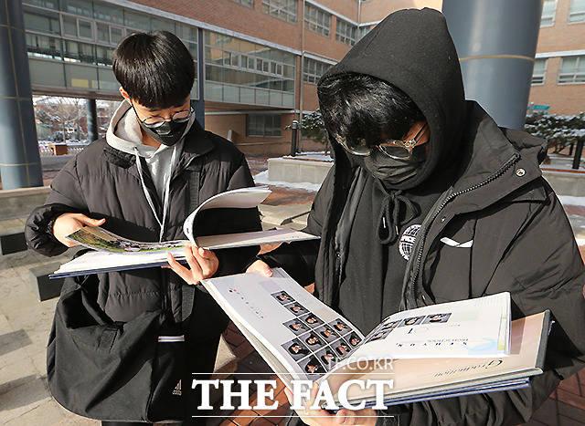 운동장에 서서 받은 졸업앨범 살펴보는 학생들