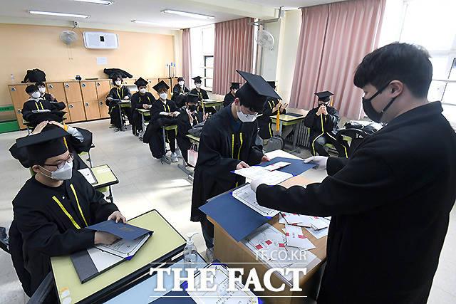 학사모와 마스크를 쓴 채 졸업장을 받는 학생들