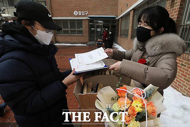 서울 세현고등학교에서 비대면 화상 졸업식을 마친 학생들이 학교로 등교해 졸업장을 수령하고 있다.