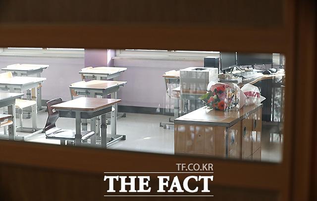 아이들 없는 교실 교탁 위에 꽃다발이 덩그라니 놓여 있다.