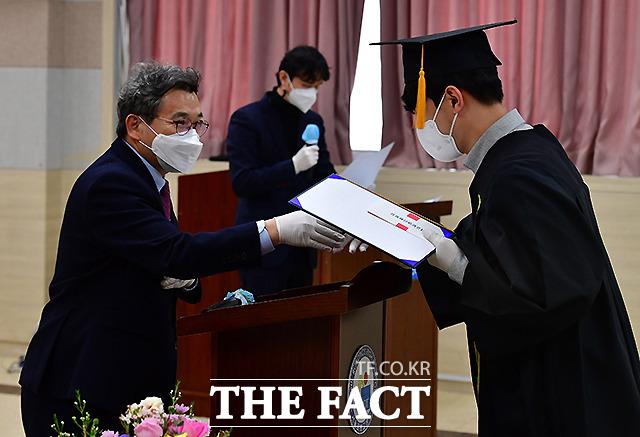 서울 로봇고등학교에서 강상욱 교장선생님이 마스크와 장갑을 낀 채 졸업장을 수여하고 있다.