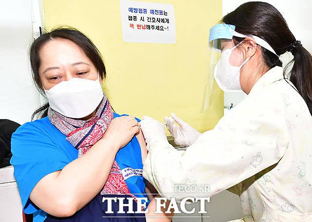 26일 오전 경기도 광명시보건소에서 첫 접종자인 강경희 씨가 백신 주사를 맞고 있다.