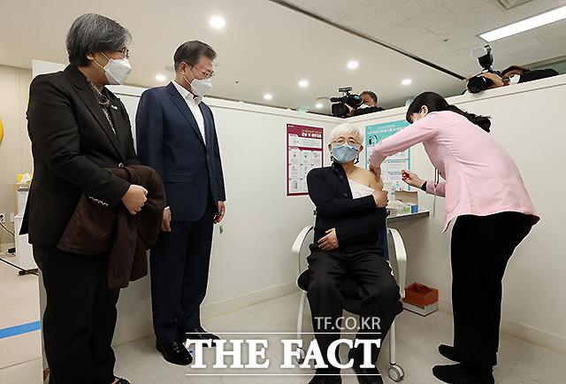 문재인 대통령과 정은경 질병관리청장(왼쪽)이 26일 코로나19 백신 접종 참관을 위해 서울 마포구보건소를 방문해 백신 접종을 받는 김윤태 푸르메 넥슨어린이 재활병원 의사를 지켜보고 있다.