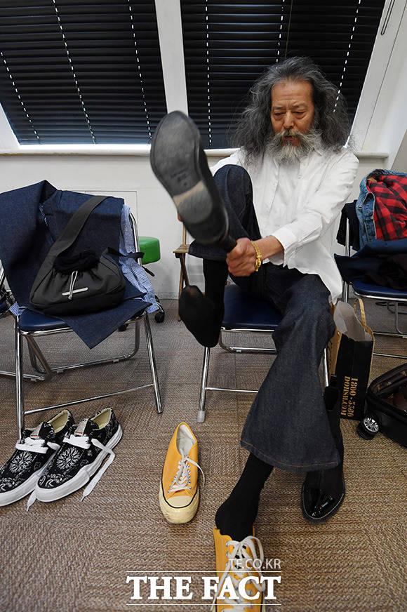 진 의류 촬영을 앞두고 본인이 직접 준비한 구두를 꺼내 신고 있는 김칠두.