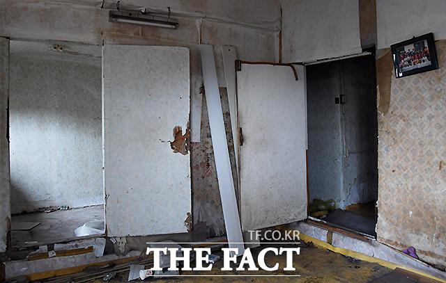 모두가 떠나고 허물어진 집안 내부, 벽에 걸린 가족사진이 눈길을 끌고 있다.