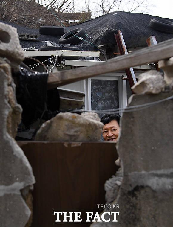 무너진 돌담 사이로 대화를 나누던 주민이 카메라에 멋쩍은 웃음을 짓고 있다.