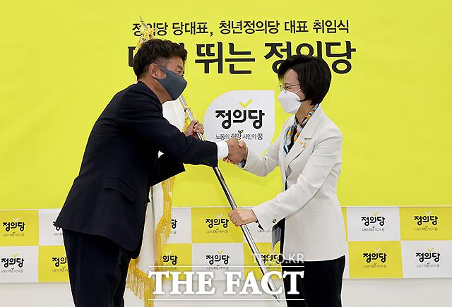 여영국 정의당 신임 대표(왼쪽)가 강은미 비상대책위원장으로부터 당 깃발을 건네받고 있다.
