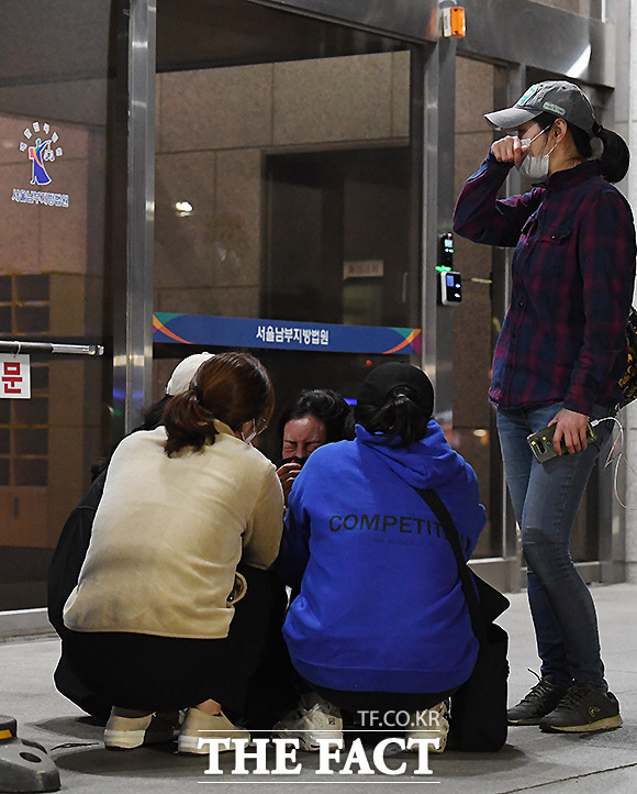 재판을 방청하고 나온 한 여성이 위로하는 시민들에 둘러싸여 눈물을 흘리고 있다.
