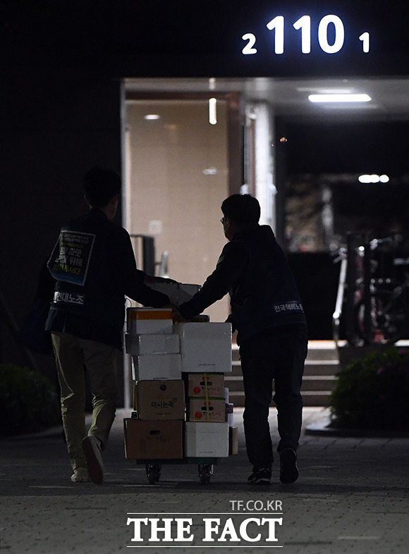 아파트 측에서 권고한 손수레를 이용해 생물 배송을 하는 택배기사들.