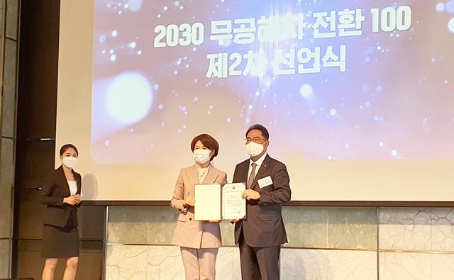 한정애(왼쪽) 환경부 장관이 14일 지준섭 NH농협은행 부행장에게 한국형 무공해차 전환100 기업 승인성을 수여하고 있다. /NH농협은행 제공