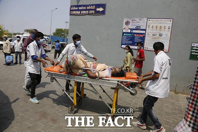 27일(현지시간) 인도 아마다바드에서 보건 종사자들이 코로나19 환자를 들것에 실어 코로나19 전용 국립 병원으로 이송하고 있다. /아마다바드=AP.뉴시스