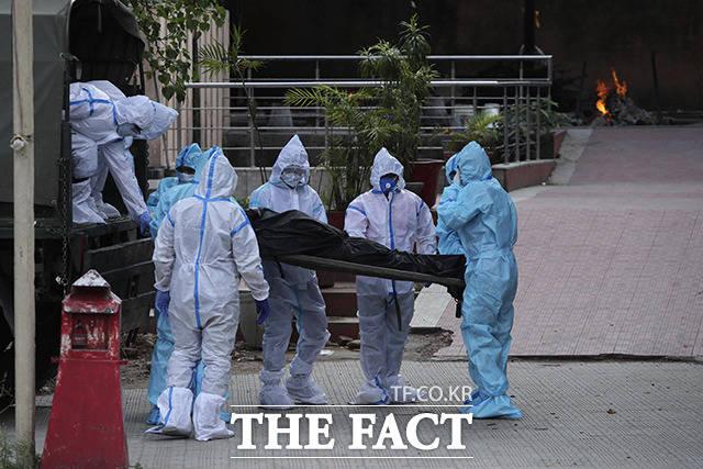 23일(현지시간) 인도 카슈미르주 잠무의 화장터에서 방호복을 입은 요원과 가족이 코로나19로 숨진 사람의 시신을 옮기고 있다. /잠무=AP.뉴시스