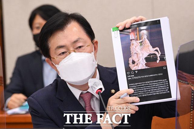 이만희 국민의힘 의원이 배우자의 도자기 불법 수입 의혹을 겪고 있는 박준영 해양수산부 장관 후보자에게 자료요청을 하며 박 후보자 배우자의 SNS 갈무리 사진을 들어보이고 있다.