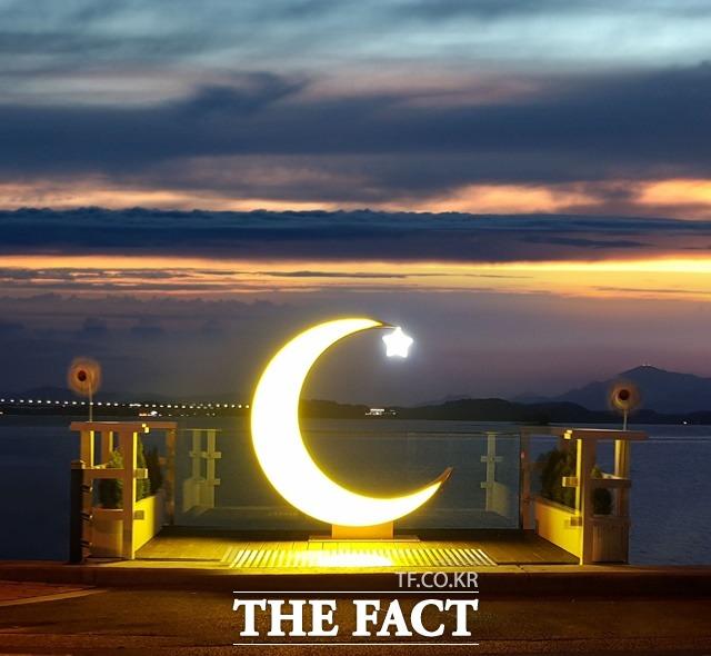 사천시 용현면 해안도로변에 설치된 포토존 노을을 픔은 초등달/사천시 제공