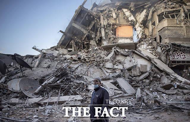 13일(현지시간) 팔레스타인 가자지구에서 한 남성이 이스라엘의 공습으로 무너진 건물을 바라보고 있다. /가자지구=AP.뉴시스