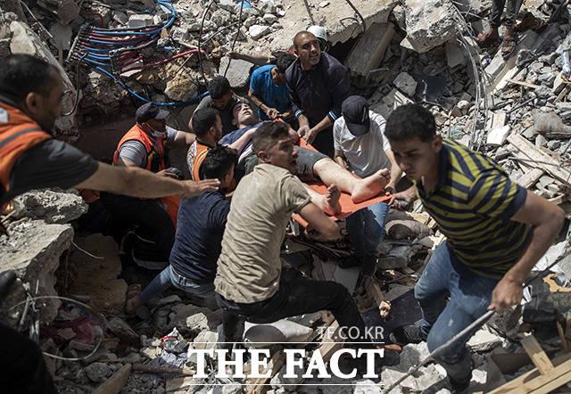 16일(현지시간) 팔레스타인 구조대가 이스라엘군의 공습으로 파괴된 가자지구의 건물에서 생존자를 구조하고 있다. /가자지구=AP.뉴시스