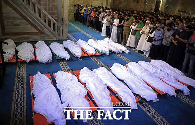 16일(현지시간) 팔레스타인 가자지구 가자시티에서 전날 밤 이스라엘군의 폭격으로 사망한 팔레스타인 주민 17명의 시신을 앞에 두고 추모객들이 기도를 하고 있다. /가자지구=AP.뉴시스