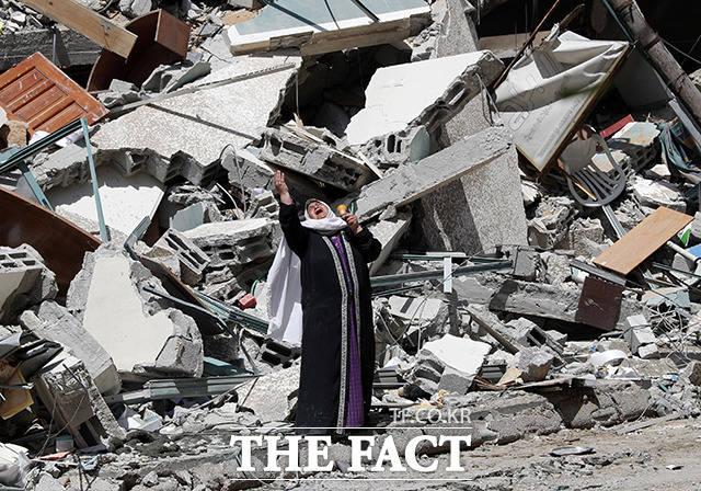 한 팔레스타인 여성이 16일(현지시간) 이스라엘군의 공습으로 파괴된 AP통신 등 언론사가 입주한 잘라 타워 잔해 앞에서 절규하고 있다. /가자지구=AP.뉴시스