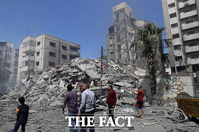 16일(현지시간) 팔레스타인 가자지구에서 현지인들이 이스라엘군의 공습으로 파괴된 건물 잔해를 바라보고 있다. /가자지구=AP.뉴시스