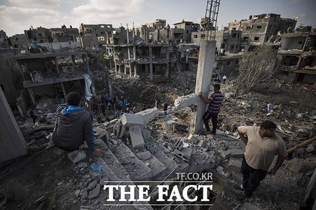 14일(현지시간) 팔레스타인 가자지구 북부의 베이트 하노운 마을에서 주민들이 지난밤 이스라엘의 공습으로 파괴된 건물들을 바라보고 있다. /가자지구=AP.뉴시스