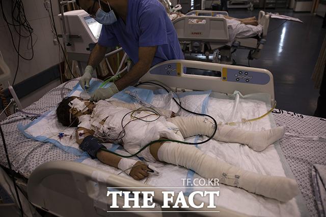 13일(현지시간) 팔레스타인 가자지구의 시파 병원 중환자실에서 한 의료인이 전날 이스라엘의 공습으로 부상한 소녀를 치료하고 있다. /가자지구=AP.뉴시스