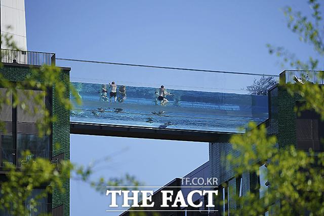 기상학적인 여름 첫날인 1일(현지시간) 영국 런던 미국 대사관 옆에 서 있는 두 개의 전용 주거 블록을 가로지르는 투명한 수영장 다리인 스카이풀에서 사람들이 수영을 하고 있다. /런던=AP.뉴시스