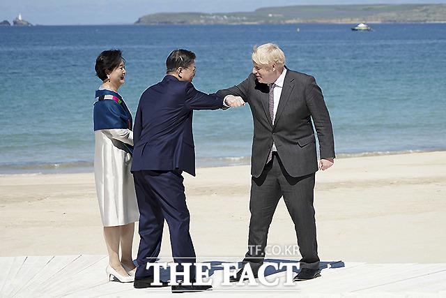 문재인 대통령과 부인 김정숙 여사가 12일(현지시간) 영국 콘월 카비스베이 해변 가설무대에서 열린 초청국 공식 환영식에 참석해 영국 보리스 존슨 총리와 인사를 하고 있다.