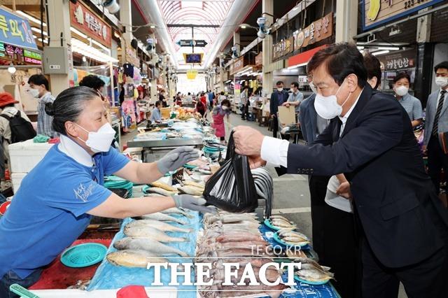 충북도교육청이 16일 전통시장 장보기 행사를 연 가운데 김병우 교육감(오른쪽)이 육거리시장에서 물건을 구매하고 있다. / 충북도교육청 제공