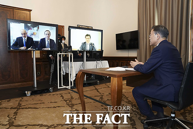 문재인 대통령이 15일(현지시간) 오스트리아 비엔나 한 호텔에서 프란츠 베르나 하스 큐어백 최고경영자(CEO)와 화상면담을 하고 있다. 오른쪽 화면은 권덕철 보건복지부 장관.
