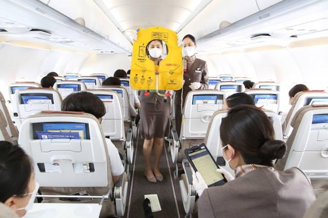 지난 18일 아시아나항공 대학생 승무원 체험 비행에 참여한 학생이 항공기 기내에서 교관 승무원과 승객 브리핑 실습을 하고 있다. /아시아나항공 제공