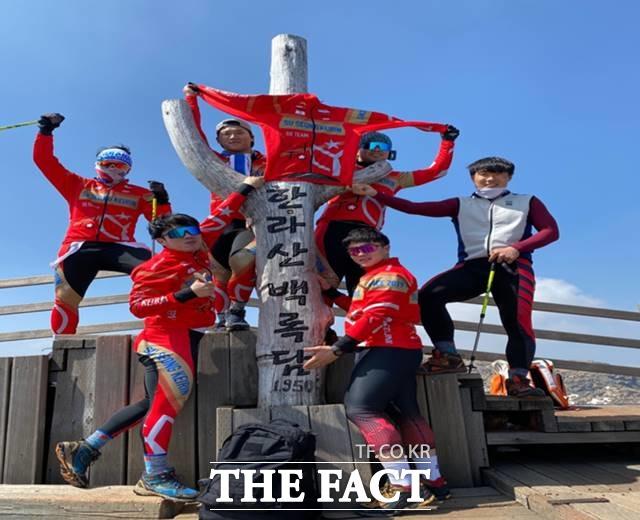 수성팀 선수들이 제주도 전지훈련 중 한라산 백록담에 올라 유니폼을 펼치며 각자 개성 있는 포즈로 기념촬영을 하고 있다./기금조성총괄본부 제공