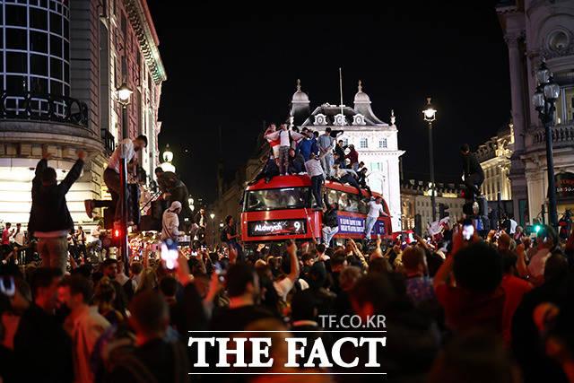 잉글랜드가 덴마크를 꺾고 유로 2020 결승전에 진출하자 7일(현지시간) 런던 시내에서 축구 팬들이 버스에 올라가 환호하며 축하하고 있다. /런던=로이터