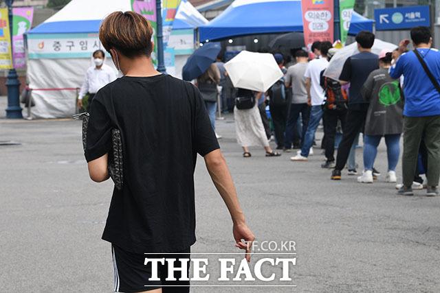 담배를 들고 당당히 걸어가며 흡연하는 남성의 모습. 오른쪽으로는 검사를 기다리는 시민들이 줄을 서 있다.