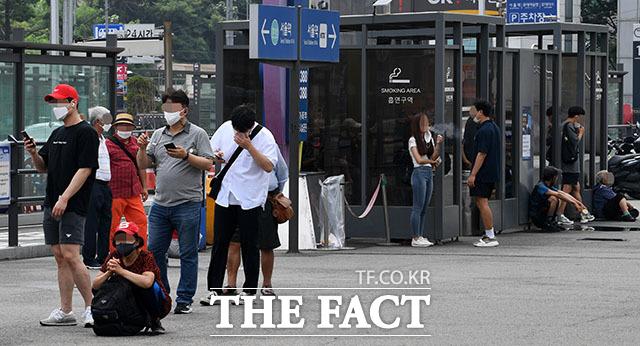 왼쪽에서 코로나19 검사를 기다리는 시민들과 흡연부스 밖에서 흡연을 하는 시민들의 모습이 대조를 이루고 있다.