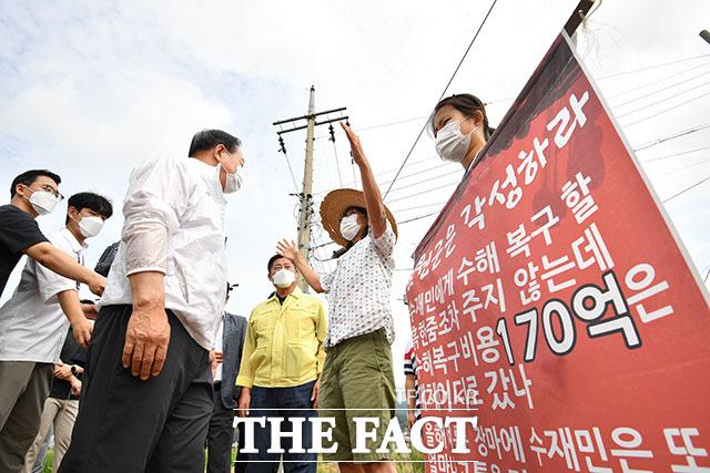이 대표가 현장 점검을 하는 가운데 한기호 국민의힘 의원(왼쪽)이 수해 피해민에게 항의 받고 있다.