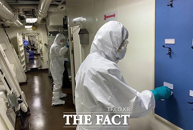 코로나19 집단감염이 발생한 청해부대 34진 전원을 국내로 이송하기 위해 출국한 특수임무단이 19일(현지시간) 문무대왕함에서 방역작업을 하고 있다./국방부 제공