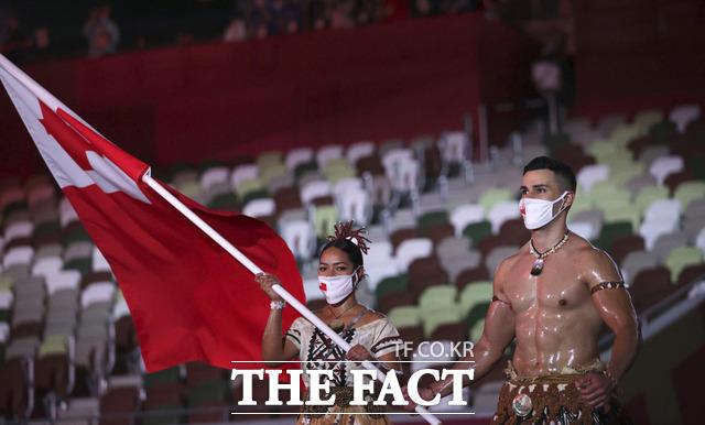 통가의 말리아 파세카와 피타 타우파토푸아(오른쪽)가 23일 오후 일본 도쿄 스타디움에서 열린 2020 도쿄올림픽 개회식에서 국기를 들고 있다. /도쿄=AP.뉴시스