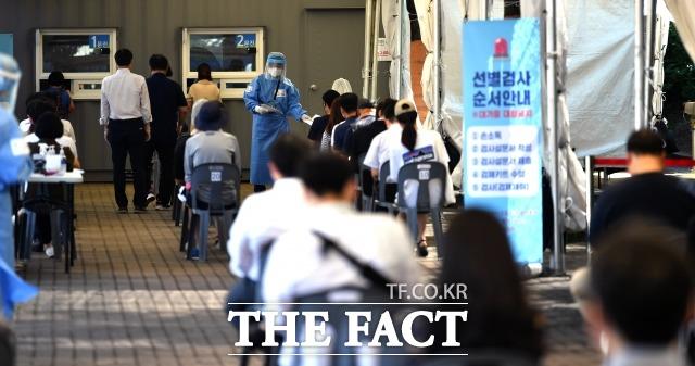 코로나19 신규 확진자가 역대 최대치인 1842명을 기록하고 있는 가운데 지난 22일 오전 서울 영등포구 여의도공원에 설치된 임시선별검사소에서 시민들이 검사를 기다리고 있다. / 더팩트DB