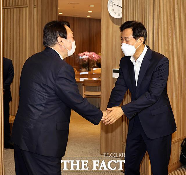 오세훈 서울시장(오른쪽)과 만나 악수 나누는 윤 전 총장.