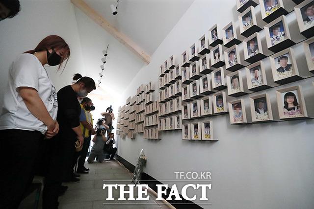 유족들이 희생자들의 사진 앞에서 묵념을 하고 있다.